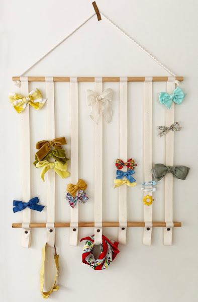 hanging bow holder - riboons hanging from dowels