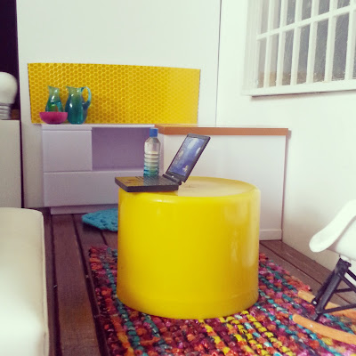 One-twelfth scale modern miniature office break-out space in bright colours with a kitchen in the background and seating and coffee tables in the foreground.
