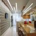 Cozinha estreita em porcelanato branca e amadeirada com ilha e parede 3D!