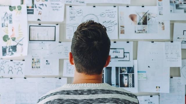 seorang pria sedang melihat data yang ditempel di dinding untuk menunjang proses belajarnya agar lebih efisien