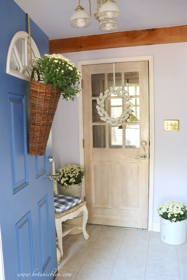 Blue front door with basket of mums and back door with white leaves wreath open into small foyer