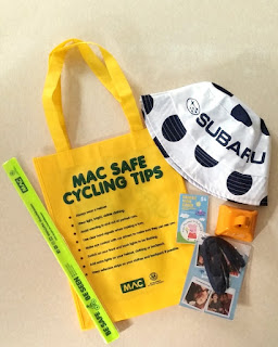 "Yellow carry bag from Motor Accident Commission (MAC) with dark green writing ""MAC Safe Cycling Tips"" and a list of 8 tips plus the MAC and State Government of Sout Australia logos. Around the bag are a black and white polka dotted king of the mountain hat sponsored by Subaru, an orange cowbell, a sponsor's promotional shoelace, a reflective arm band, set of 10  Peppa Pig stickers."
