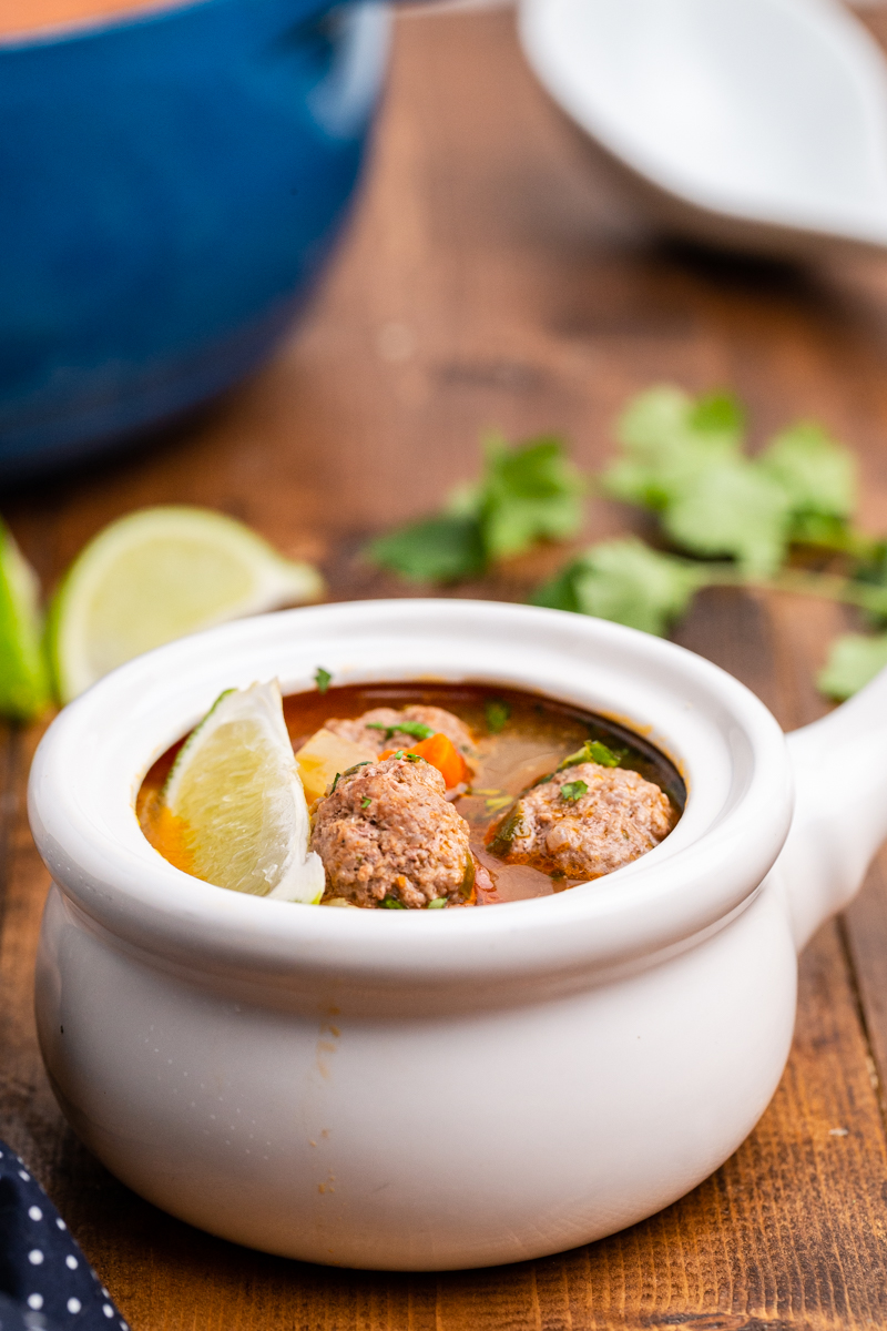 Closeup side view photo of Keto Albondigas (Meatball) Soup in a white bowl with a large blue soup pot in the background.