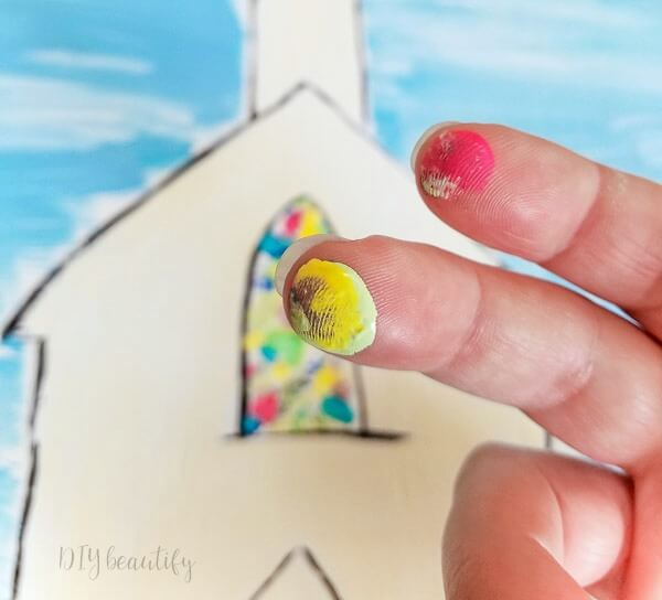paint stained glass window with fingertips dipped in paint