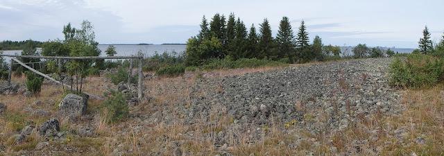 Panoraamakuva soraikkoisesta saaren rannasta jossa on vanhoja puurakenteita pystyssä
