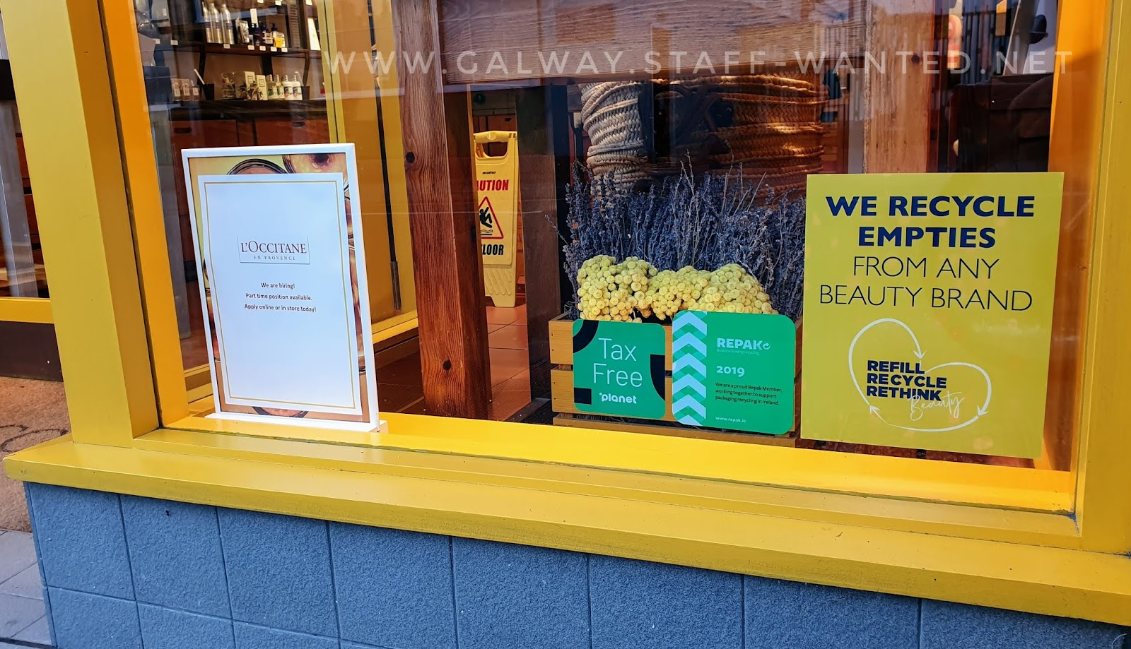 Portion of the lower front window of a shop, featuring a sign that say we recycle empty contains from perfumes of any brand