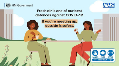 If meeting up, outdoors is safest UK Gov drawing of 2 ladies sitting outside drinking wine and chatting