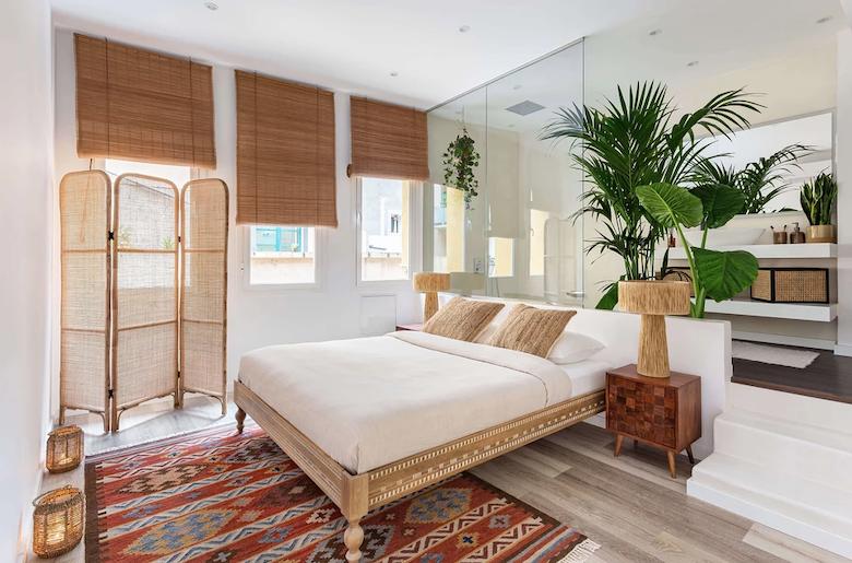 Dormitorio con decoración tropical: cama balinesa, biombos y persianas de mimbre.