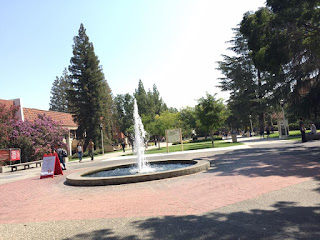A fountain rises in front of the old administration building at fresno city college. The two story building stands at the end of a walkway and is built of red brick, with steps going up to the front door.