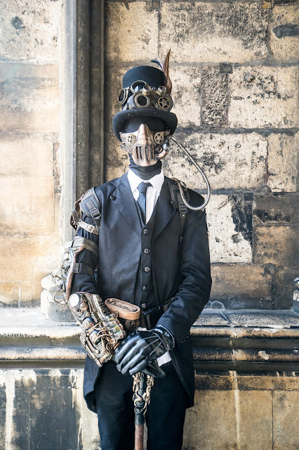 Steampunk man wearing black spandex skin suit/bodysuit costume with a 3 piece suit, top hat, goggles, gauntlets, bracers, mask and cane. mens steampunk costumes
