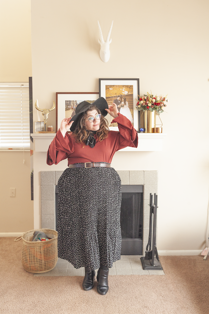 An outfit consisting of a wide brim hat, reddy orange tri tried sleeve blouse tucked into a black and white dotted pleated maxi skirt and black chelsea boots.