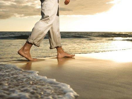 Homem caminhando na praia