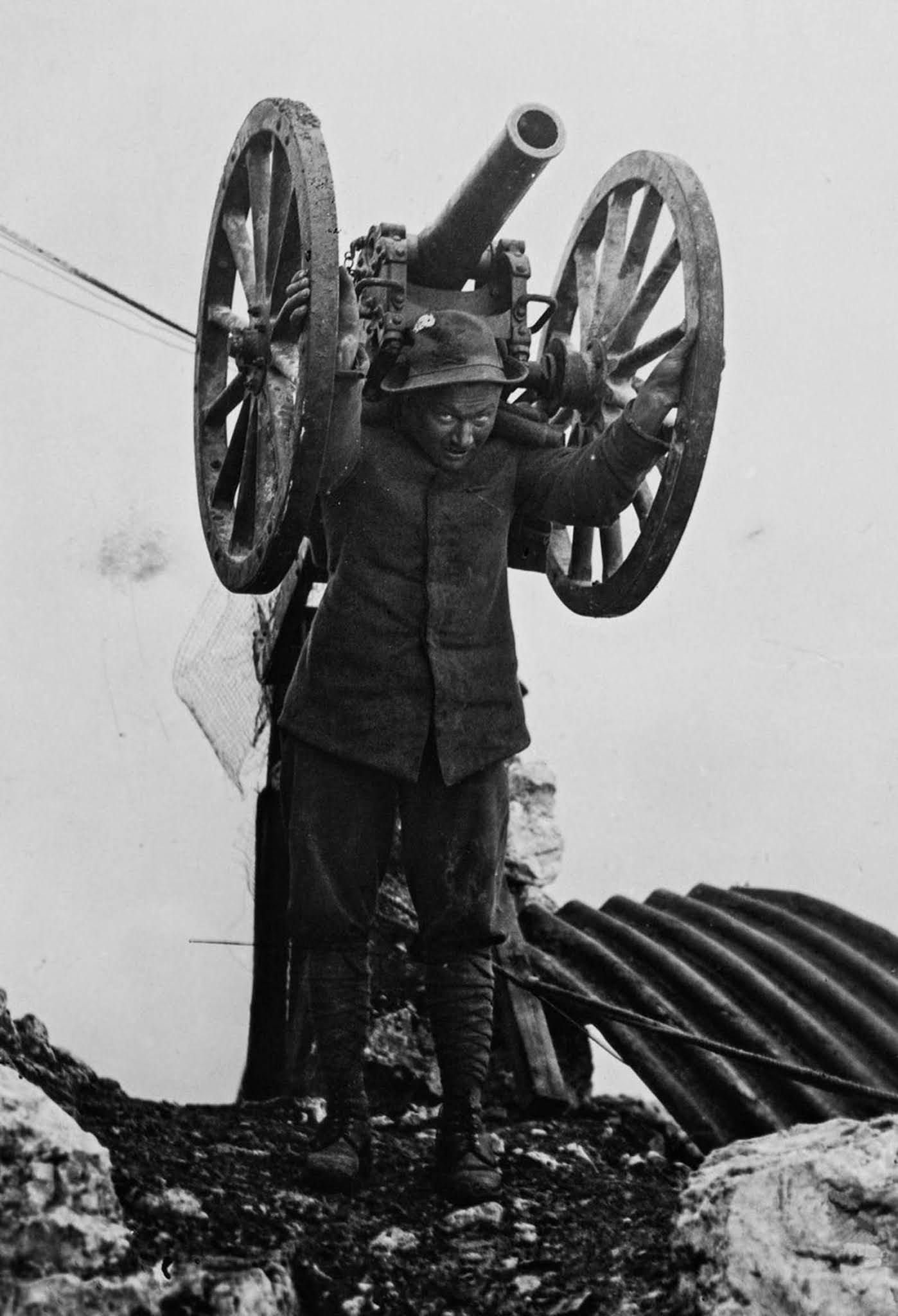 A soldier carries a field gun to higher ground. 1916.