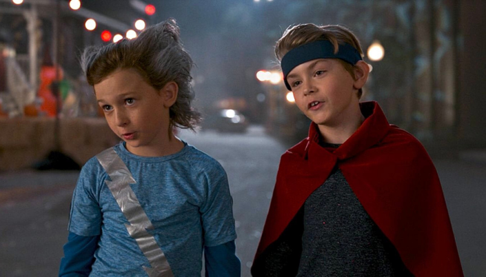 Imagem: Tommy, em uma fantasia de Mercúrio, uma camisa azul-clara com um raio prateado descendo do ombro até o lado esquerdo, os cabelos arrepiados e com tinta prateada e ao lado Billy, em uma camisa cinzenta, uma capa vermelha e uma bandana azul-escura ao redor do cabelo.