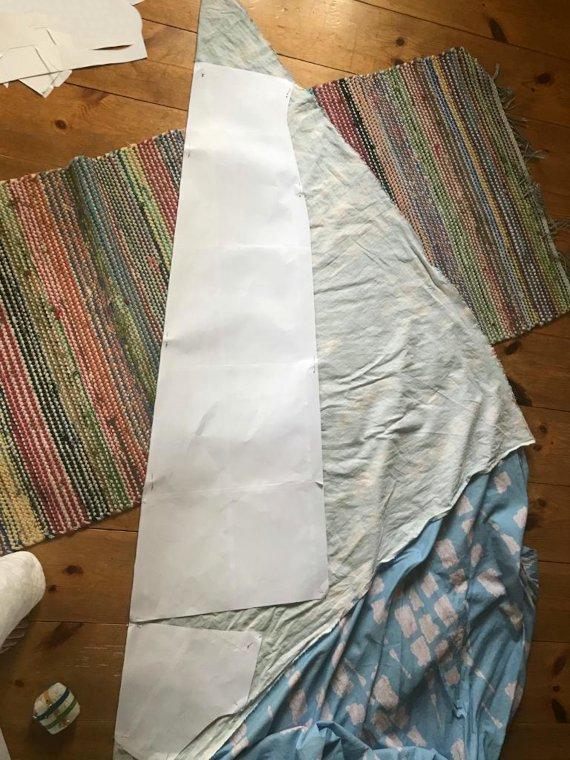 Puulattialla on räsymättö, jonka päälle kangas on taitettu vinonlangansuuntaan. Kuvassa näkyvät myös kuvaajan varpaat.