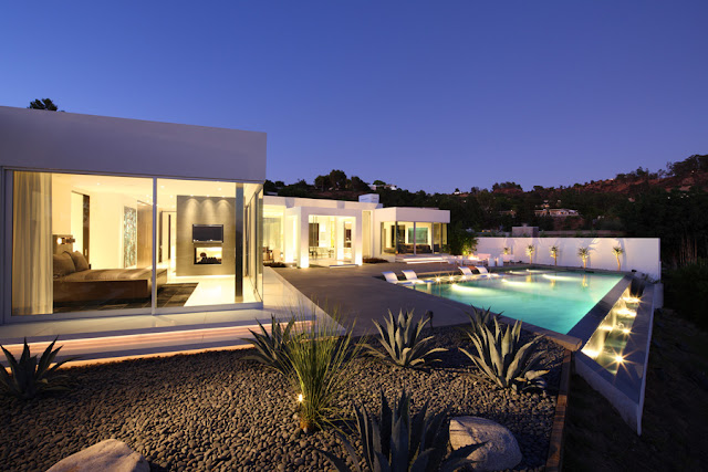 Modern home and its swimming pool at night