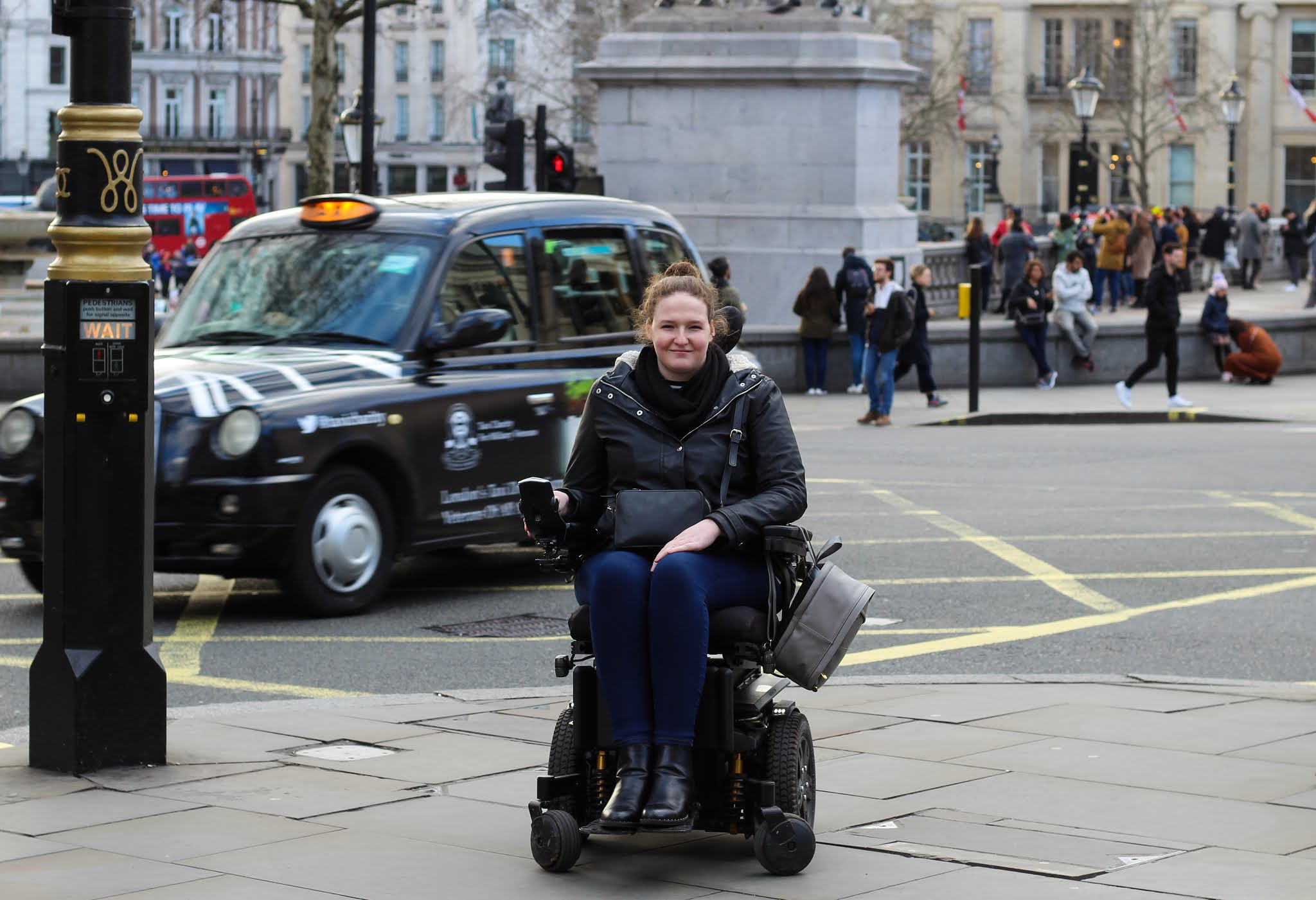 Shona, a young woman with auburn hair tied back is sitting in her powerchair. She is wearing navy jeans, black boots, a black coat and has a grey bag hanging off one of her armrests. She is in the middle of a busy London area, by Trafalgar Square. Red buses and black taxis can be seen behind her.
