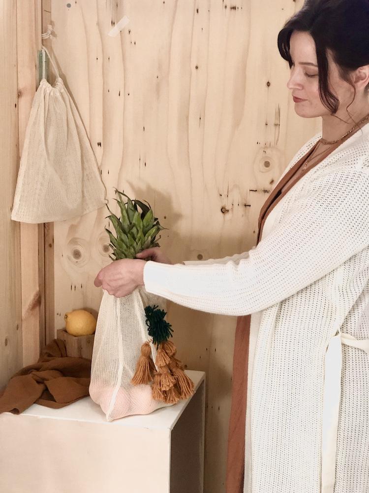 Nainen laittaa hedelmiä tupsuilla tuunattuun kestohedelmäpussiin