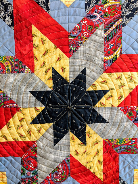 An orange peel design surrounded by spiral quilting on a Lone Star quilt