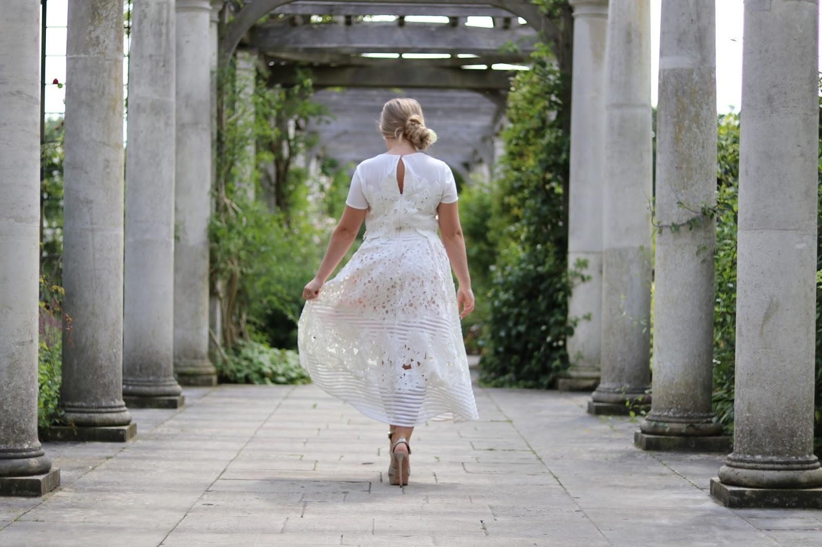 Katie Heath wearing white Janelle Ted Baker Wedding Dress and Kurt Geiger Gold Heels in Hampstead Pergola, London
