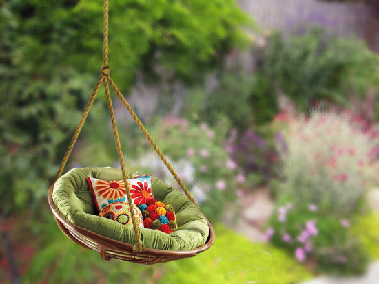 Purchase a papasan chair. They cost a fraction of the price. Buy strong,  medium sized rope and hang it! It can be hung outdoors from a tree branch.