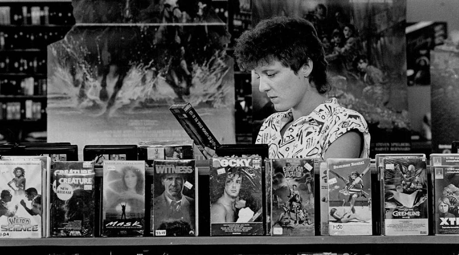 Employee Tammy Swier looks at VCR cassettes tapes at Colfax Video. 1986.