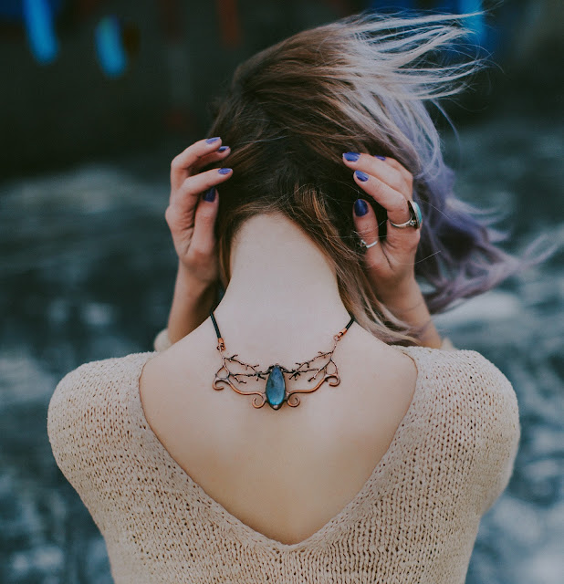 A brunette woman with her back facing the camera showing an intricately-designed necklace.