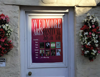 Pic of Wedmore Arts Festival poster on door and flowers either side