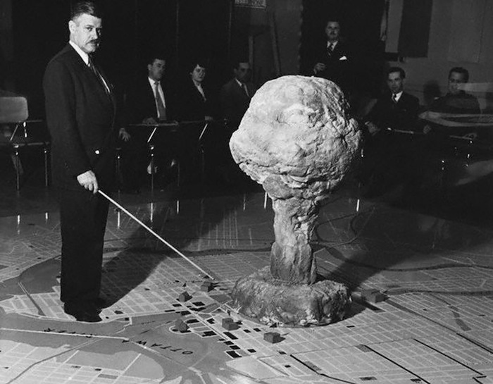 40 Amazing Historical Pictures - The commandant of the Civil Defense Technical Training Centre in Quebec demonstrates the effect of an atomic bomb exploding over a city