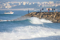 6 Surfers eye a set coming while the fishermen go on about their day on the breakwall 2018 Caparica Pro foto WSL Laurent Masurel