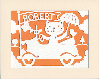 Papercut picture of a cat in a car