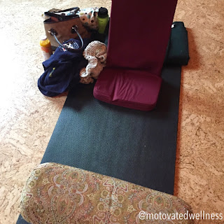 Yoga mat with bolsters and personal belongings to the side