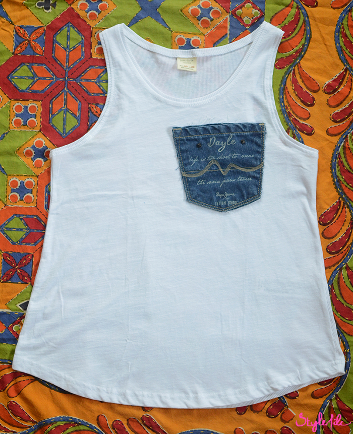 White t-shirt with denim pocket patch trend on the top corner placed on a colourful fabric with embroidery