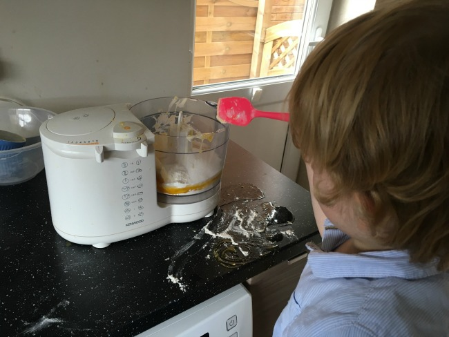 toddler-with-a-pink-spoon-and-a-food-processor-and-a-mess-of-eggs-and-flour-on-the-work-top