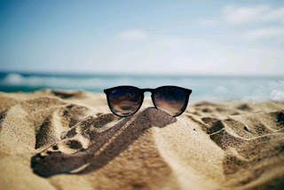 Black sunglasses on the sand with the sea in the background