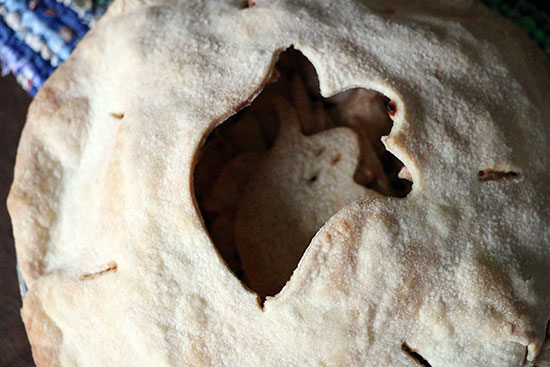 Close up of top of apple pie with a ghost shape cut out of the center of the crust.