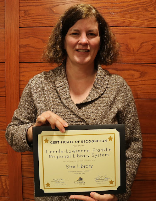 smiling woman holds a certificate of recognition for lincoln lawrence franklin regional library system