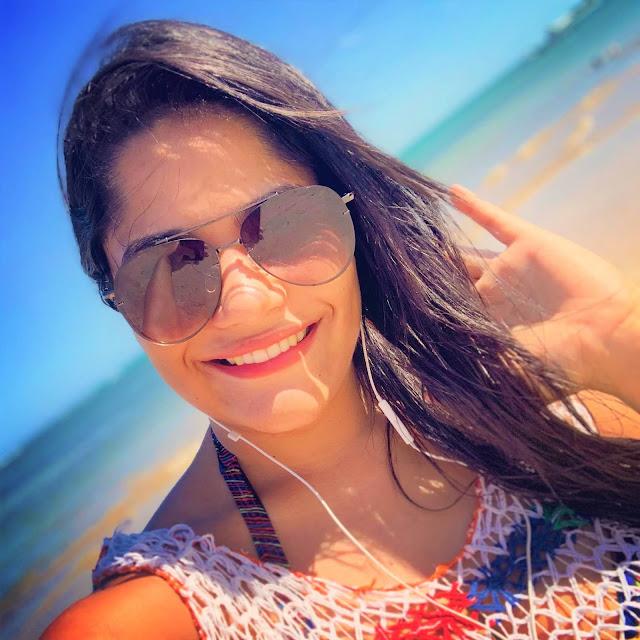 mulher com óculos escuro e saída de banho colorida na praia