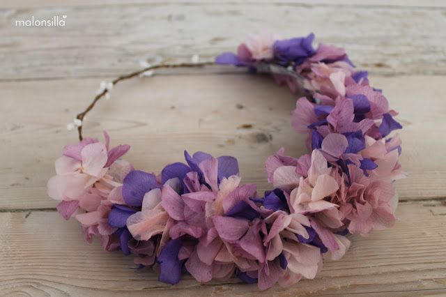 Diadema de flores naturales preservadas en color morado y lila sobre suelo de madera