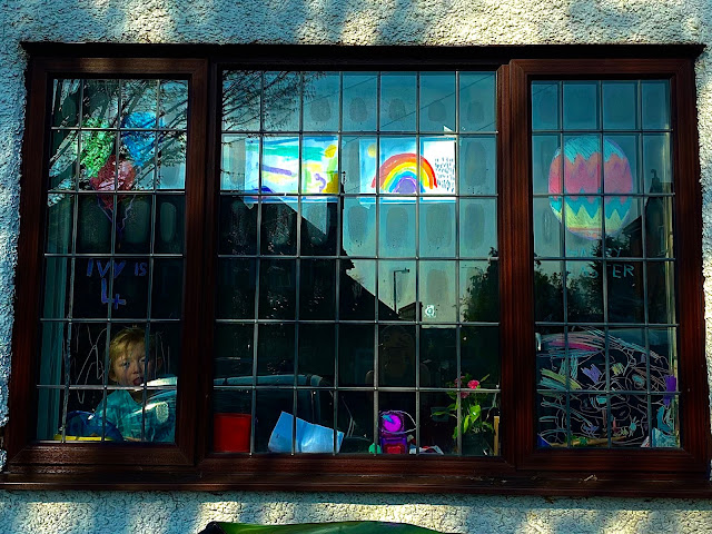 A front window with some rainbow artwork, a drawing of balloons and a birthday message and an easter egg