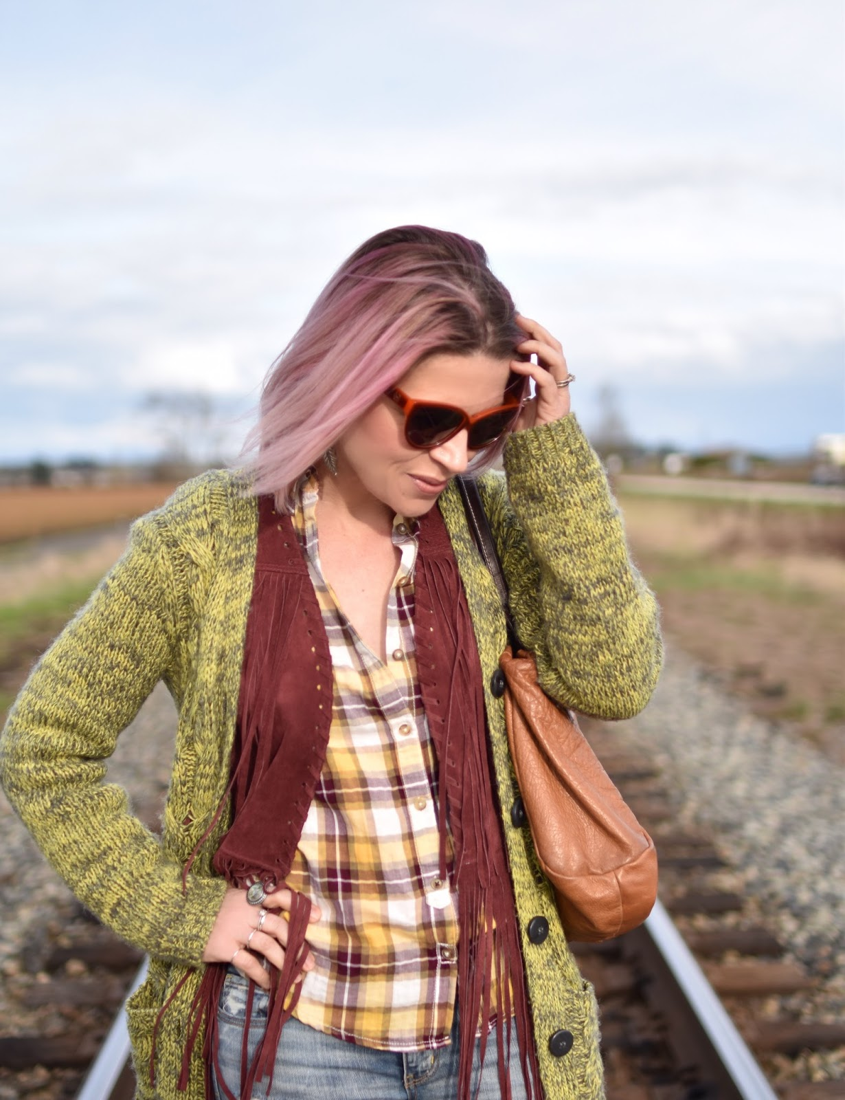 Monika Faulkner outfit inspiration - plaid shirt, fringy vest, slouchy cardigan, cat-eye sunglasses