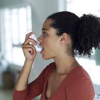 Woman using her inhaler for asthma symptoms