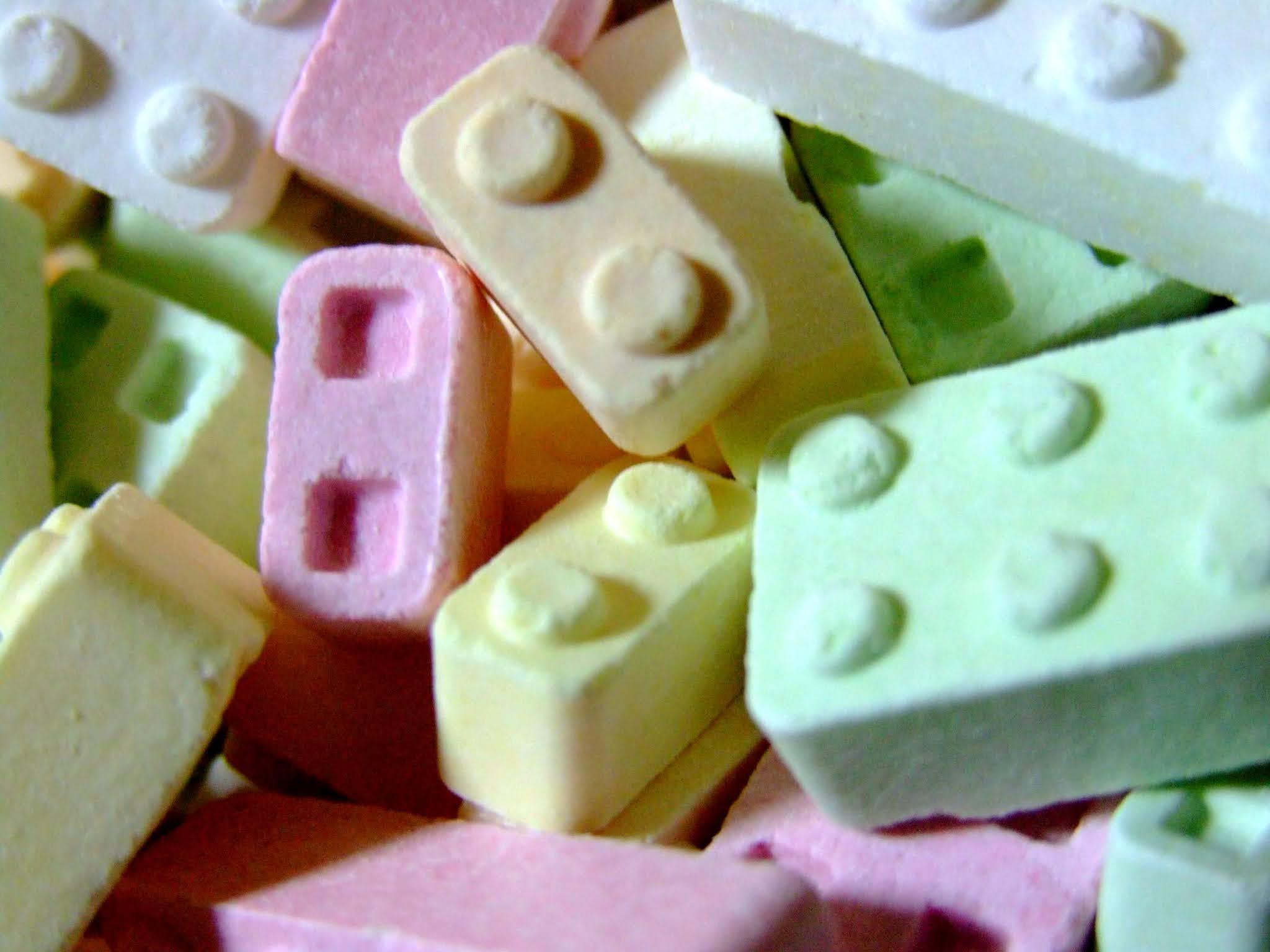 ブロックの形が楽しくてワクワクする、可愛いラムネ菓子の写真素材です。優しいパステルカラーが画面を引き立てますよ。