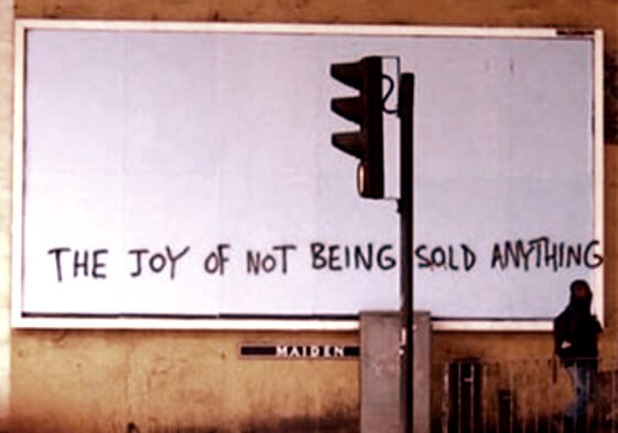 "Street-side billboard reads, ""The Joy of Not Being Sold Anything."""