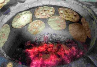 Cooking tandoori roti in a charcoal Ovalclay tandoor