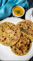 Serving three pieces of onion kulcha, dal 8n background