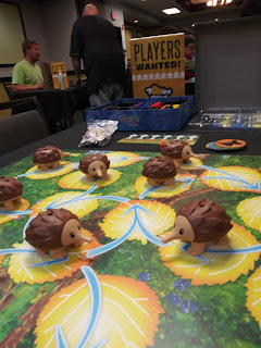 A game of Echidna Shuffle ready to play. The board, consisting of a bunch of leaves with arrows indicating the direction of travel, with several adorable plastic echidna figurines distributed across it. Behind the board, a 'Players Wanted' sign can be seen.