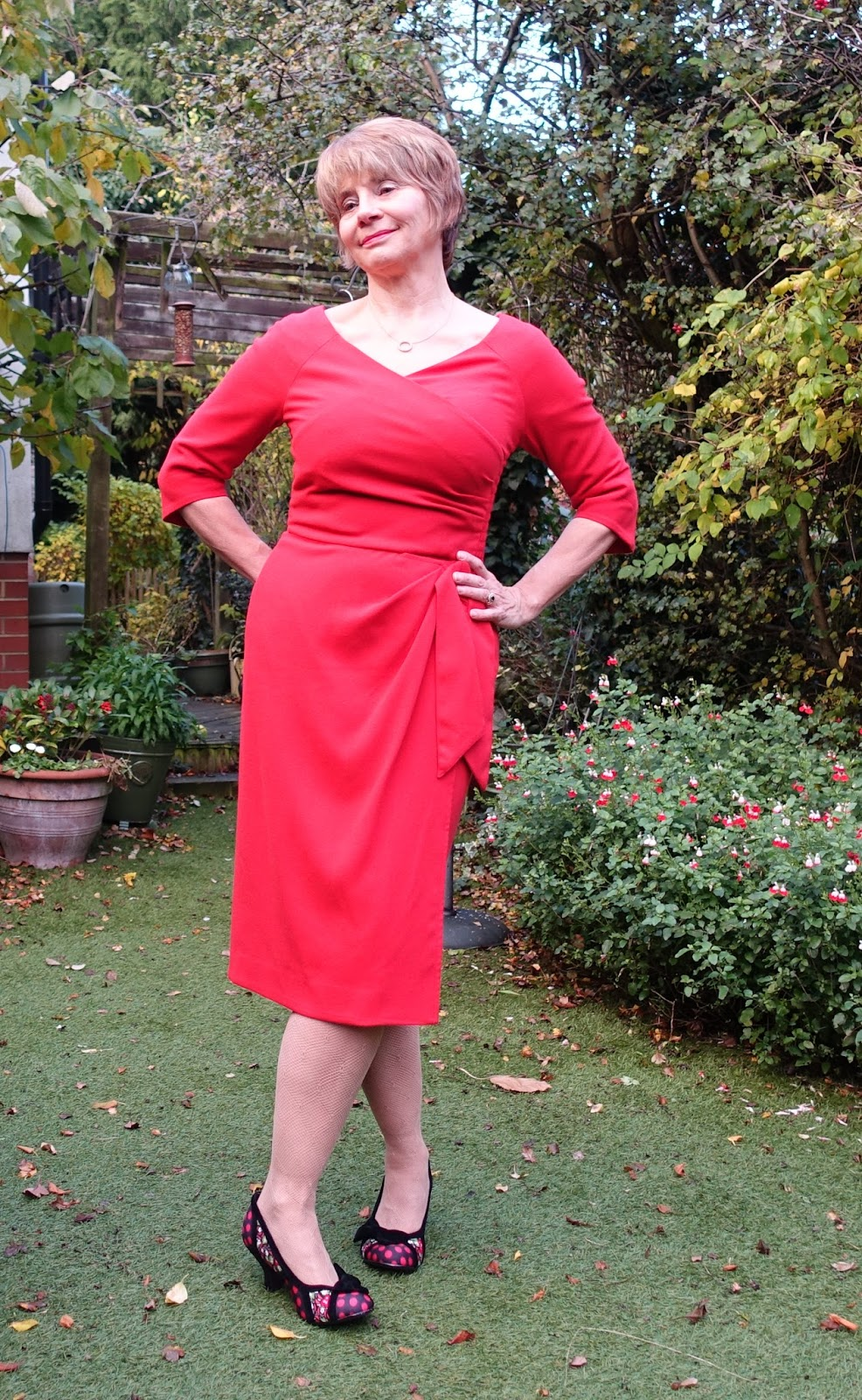 Image showing a 50 plus woman in the garden wearing a red Bombshell dress