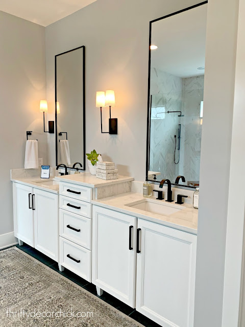 Modern master bath with white cabinets and black accents