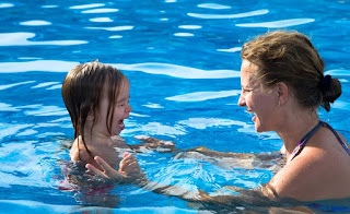 Image of child and adult in the water: This article is about here is how to choose swimming lessons